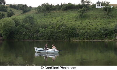 Just married couple on floated boat slides through the water