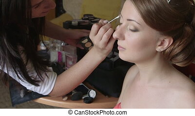 Bridal makeup artist applying eyeshadow
