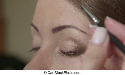 Makeup artist applying eye shadow - Makeup artist helped the...