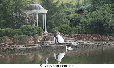 Newlyweds on the steps by the pond in the park