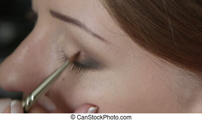 Makeup artist applying shades - Makeup artist using brush to...