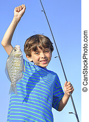 Young fisherman - Young handsome boy holds up a fish he...