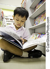 Child reading a book - Children reading a book shelf in the...