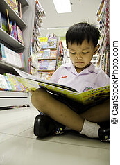 Child reading a book. - Children reading a book shelf in the...