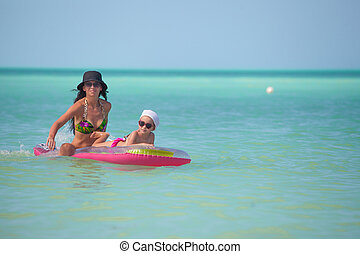 Young mother with young daughter on an air mattress in the sea