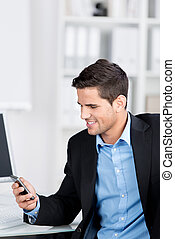 Businessman smiling while looking at his mobile