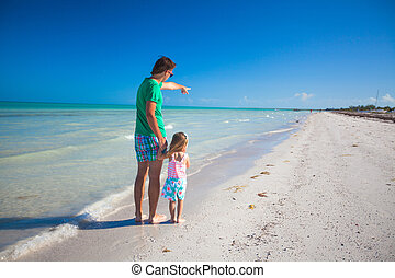 Rear view of young father with his daughter shows in the sea