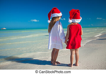 Two little cute girls in Christmas hats have fun on the...