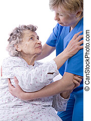 nurse with a senior woman - nurse helps the senior woman get...