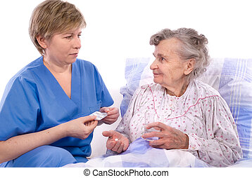 nurse with a senior woman - nurse gives the senior woman the...