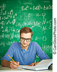 Graduation test - Portrait of handsome student carrying out...