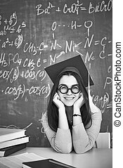 Alumna - Black-and-white image of student in graduation hat...