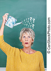 Teacher Holding Watering Can With Question Marks On...