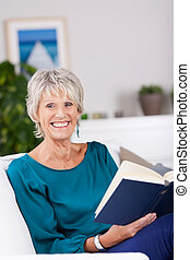 Mature woman reading - beautiful mature woman reading in a...
