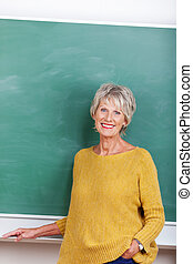 Mature lady teacher - Attractive mature teacher standing in...