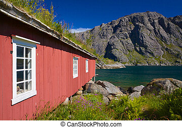 Fishing hut by fjord - Traditional old red fishing hut with...