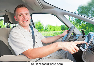 Man in car - Happy man in the car using his mobile as a...