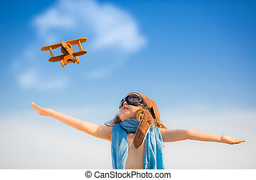 Happy kid playing with toy airplane against blue summer sky...