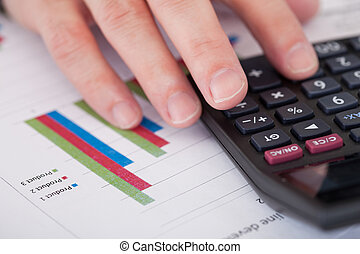 Close-up Of A Businessman Hand Analyzing Stock Charts