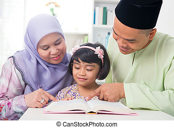 Malay Muslim family reading a book. - Malay Muslim parents...