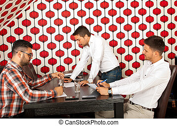 Business meeting - Three business men having meeting in a...