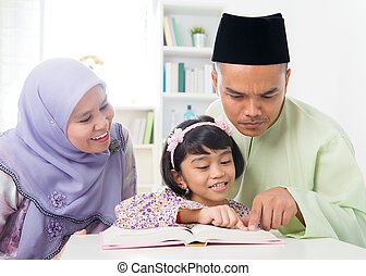 Malay Muslim parents teaching child reading a book....