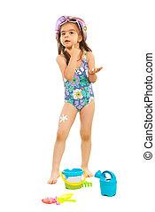 Girl applying sunscreen on face - Little girl in swimsuit...