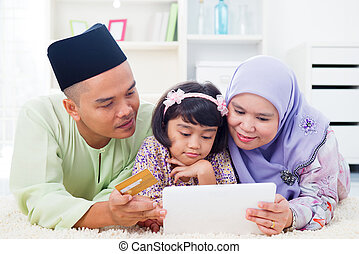 Asian family online shopping - Southeast Asian family using...