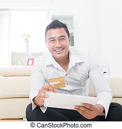 Shop on the internet - Attractive Southeast Asian man using...