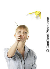 Origami plane - Young blond woman throwing yellow origami...