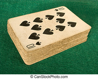 Old deck of cards on a green baize poker table.