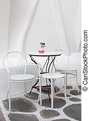 White table and chairs in the cafe with flowers on the...