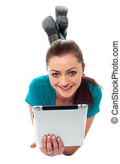 Pretty girl browsing on her tablet pc - Portrait of a...