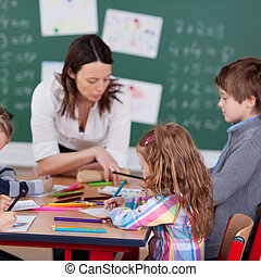 Busy students with teacher - Portrait of teacher helping her...