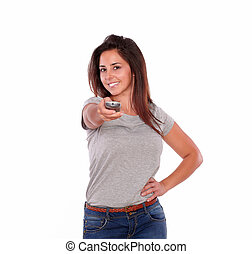 Smiling young woman pointing with remote control
