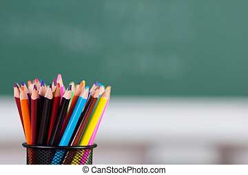 Colorful pencil on holder over the blackboard background