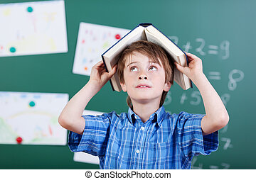 Young elementary schoolboy with a book over head