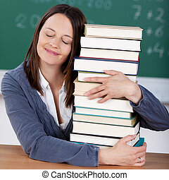 Stack of books - Loving teacher embracing a pile of books at...