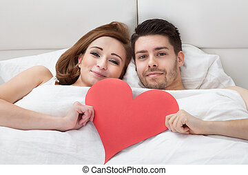 Portrait of young loving couple lying on bed holding heart