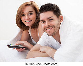 Young couple watching television - Young couple lying on...
