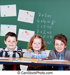 Three children sitting over the blackboard background