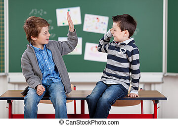 Two male students - Two young male students giving each...