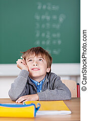 Schoolboy daydreaming when sitting at his desk - Schoolboy...