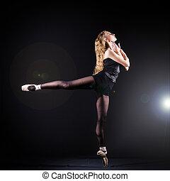 Ballerina dancing in the dark studio