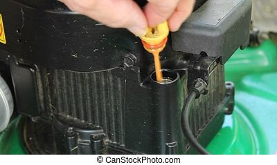 checking the oil on a small lawnmower