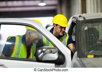 warehouse workers inspecting vehicle