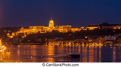 Buda Castle (Royal Palace) by the Danube river illuminated...