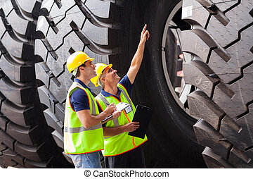 shipping company workers checking industrial tires before...