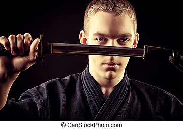 kendo warior - Handsome young man practicing kendo Over dark...