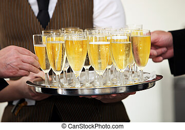 Tray of chilled champagne in elegant flutes being carried by...